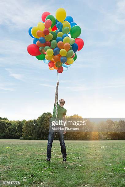 Man holding colorful balloons