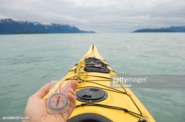 Man holding compass while sea kayaking, personal perspective