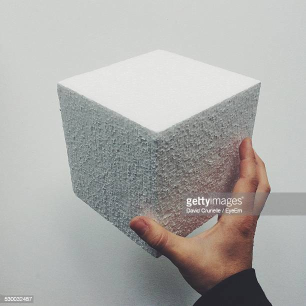 Man Holding Concrete Cube Against Wall