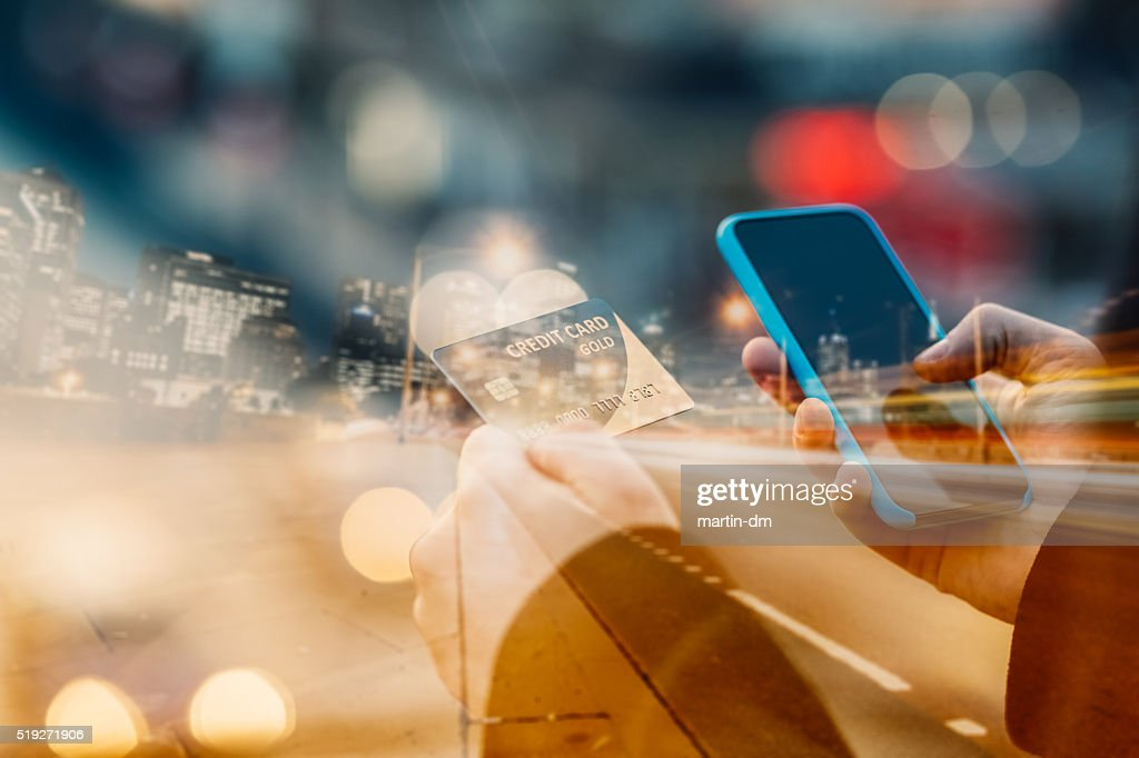 Man holding credit card and texting : Stock Photo