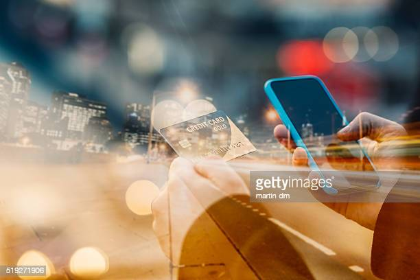 man holding credit card and texting - online shopping stock photos and pictures