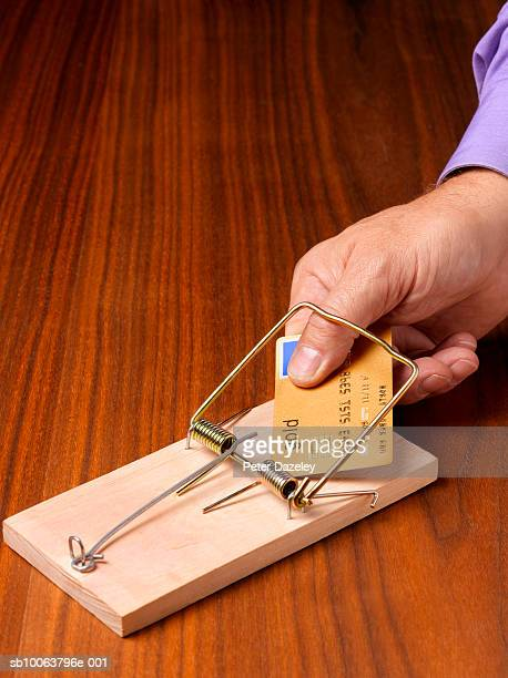 Man holding credit card in mouse trap, close-up