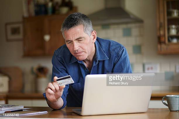 Man holding credit card using laptop in kitchen