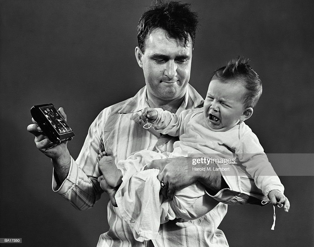 Man holding crying baby (21-24 months) and alarm clock (B&W) : Stock Photo