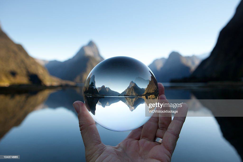 Man holding crystal ball in landscape : Stock Photo