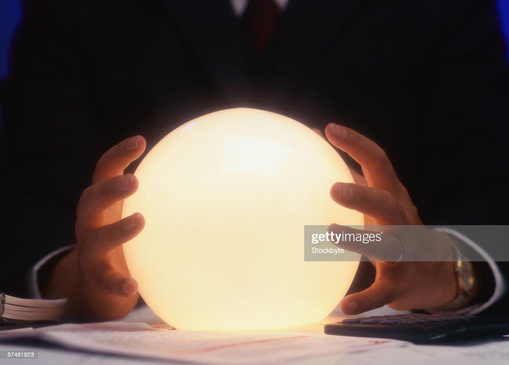 man holding crystal ball : Stock Photo