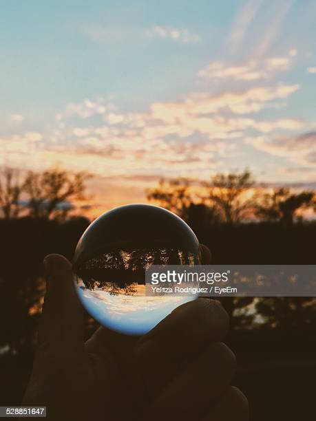 man holding crystal ball with reflection of lake and trees in it - unusual angle stock pictures, royalty-free photos & images