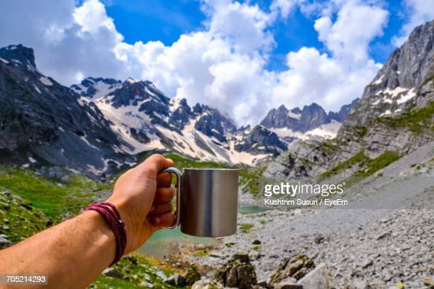 Man Holding Cup Against Mountain Range