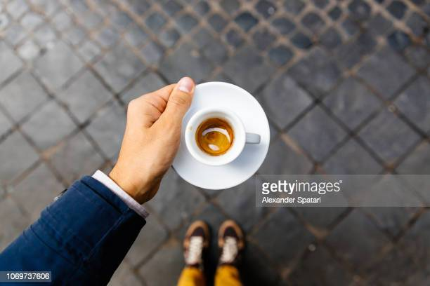 man holding cup of espresso coffee, personal perspective view - élégance photos et images de collection
