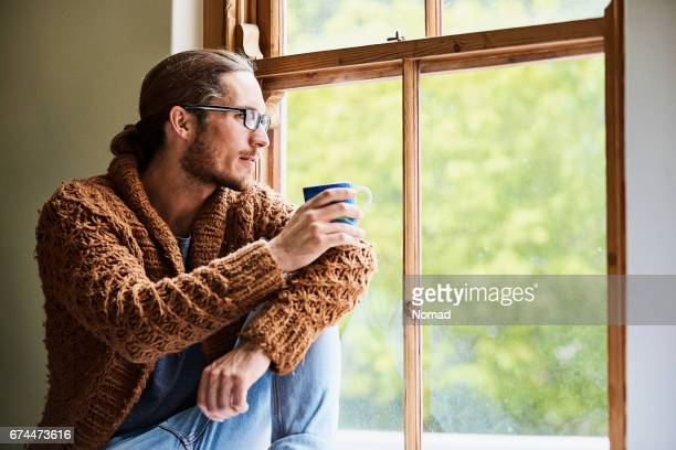 man holding cup while looking through window - one man only stock pictures, royalty-free photos & images