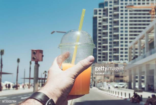 Man holding cup with fresh squeezed orange juice
