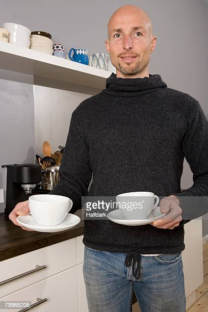 Man holding cups in the kitchen