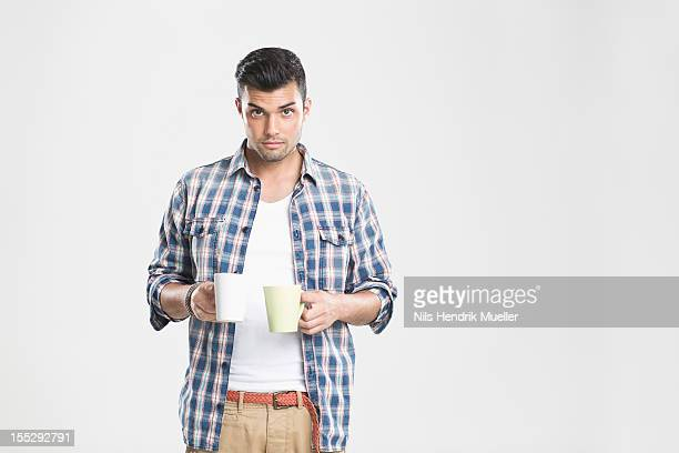 man holding cups of coffee - two objects stock pictures, royalty-free photos & images