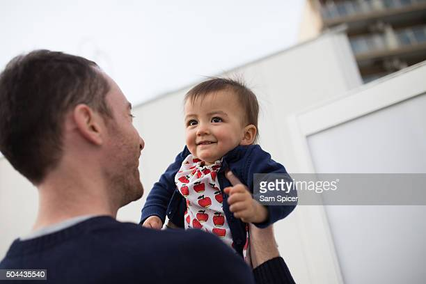 man holding cute baby - leanintogether stock pictures, royalty-free photos & images