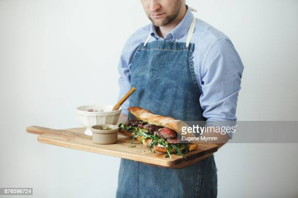 Man holding cutting board with grilled steak sandwich