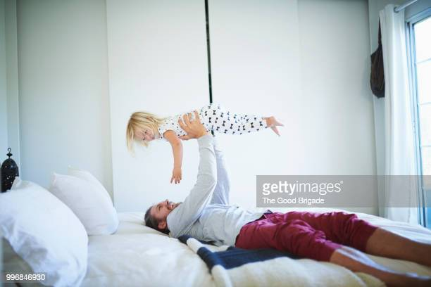 Man holding daughter in air while lying in bed