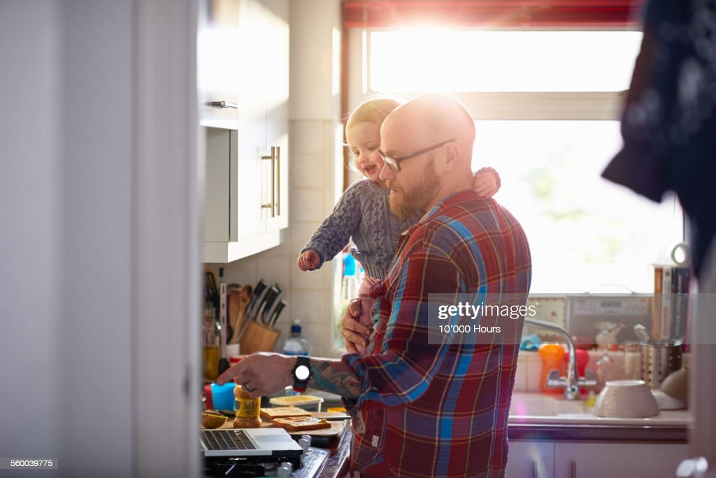 Man holding daughter whilst using laptop : Stock Photo