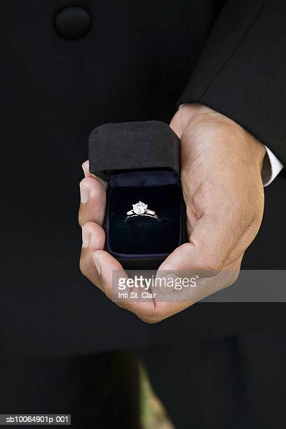 Man holding diamond ring in box, mid section, close-up of hand