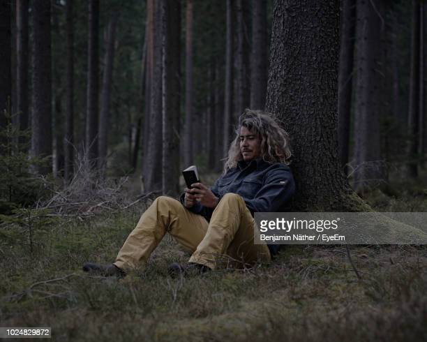 Man Holding Diary While Leaning On Tree Trunk In Forest