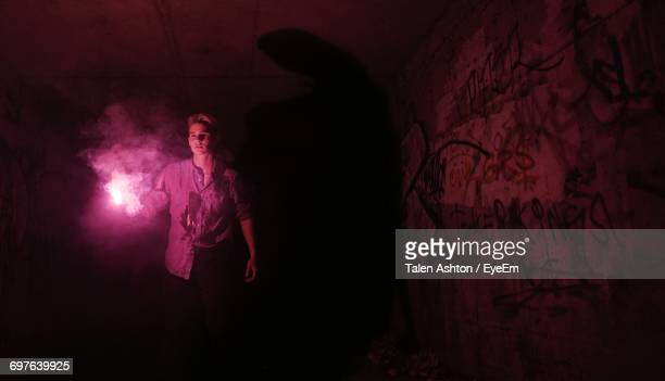 Man Holding Distress Flare While Walking In Tunnel