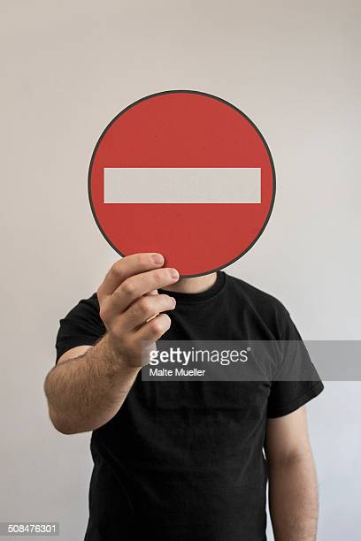 Man holding do not enter sign emoticon in front of his face
