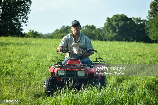 man holding dog while riding quadbike in field - lap dog stock pictures, royalty-free photos & images
