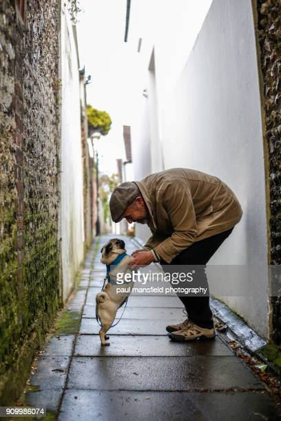 Man holding dog's paws in passageway