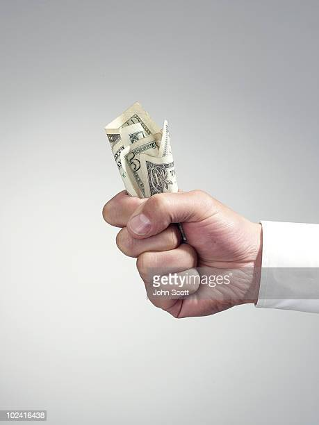 Man holding dollar bills, close-up of hand