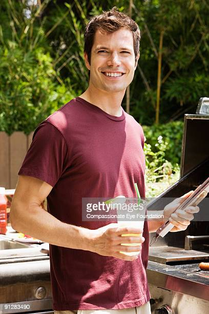 Man holding drink and bbq utensils