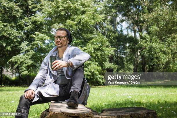 man holding drink while sitting in park - hand on knee stock pictures, royalty-free photos & images
