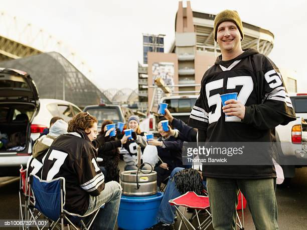 man holding drinks at tailgate party, friends in background - tailgate party stock pictures, royalty-free photos & images