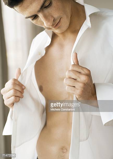 Man holding edges of unbuttoned shirt