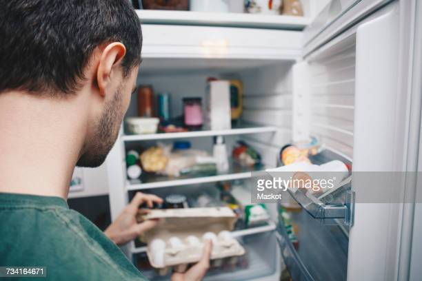 man holding egg carton by refrigerator in kitchen - geladeira - fotografias e filmes do acervo