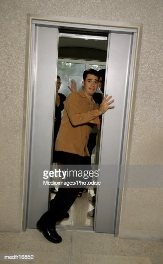 Man Holding Elevator Door Open With Funny Look On His Face
