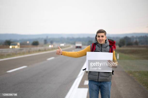 man holding empty cardboard while hitchhiking - hitchhiking stock pictures, royalty-free photos & images