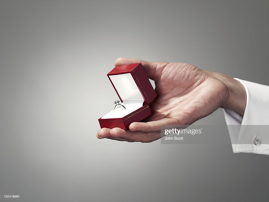 Man holding engagement ring, close-up of hand : Stock Photo