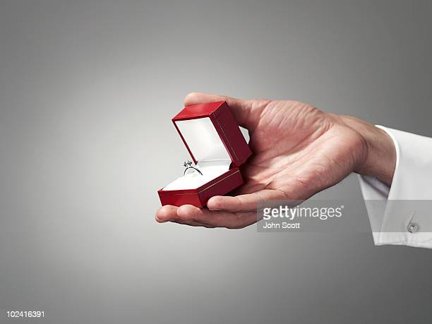 man holding engagement ring, close-up of hand - anello gioiello foto e immagini stock