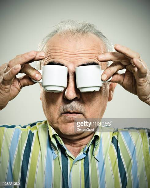 man holding espresso cups to eyes