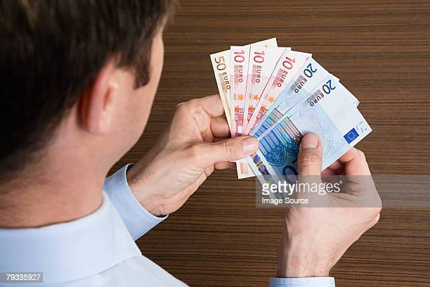 man holding euros - twenty euro banknote stock photos and pictures