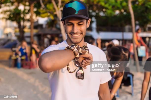 man holding exotic snake around his hand, kuta, bali, indonesia - exotismo fotografías e imágenes de stock