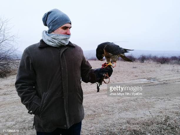 Man Holding Falcon On Field Against Sky