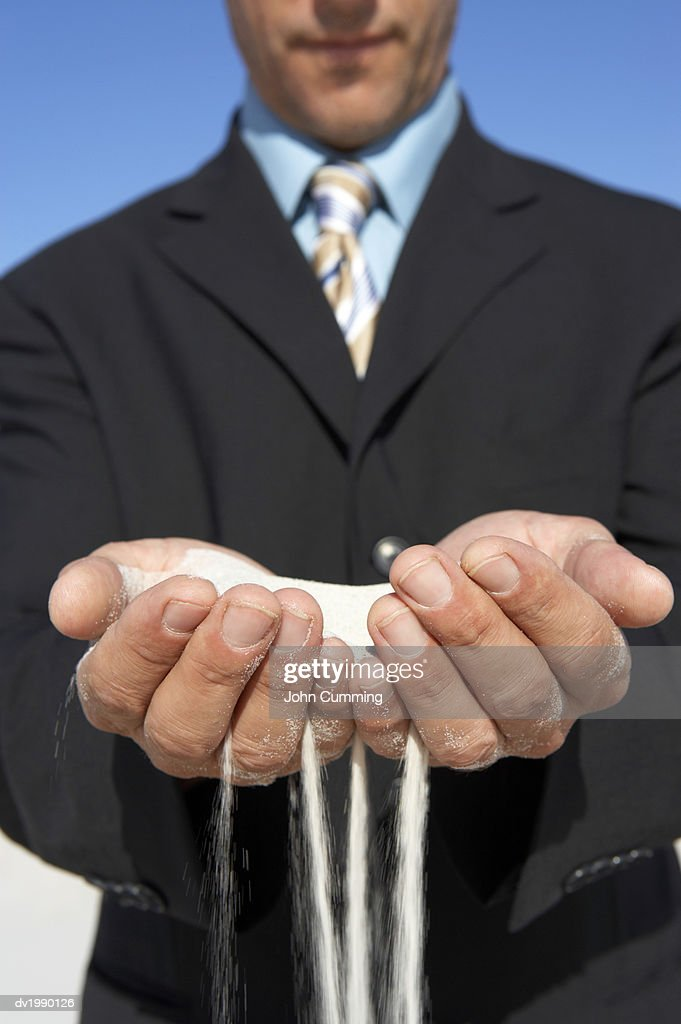 Man Holding Falling Sand in His Hands : Stock Photo