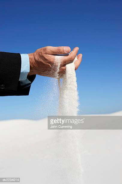 Man Holding Falling Sand in His Hands