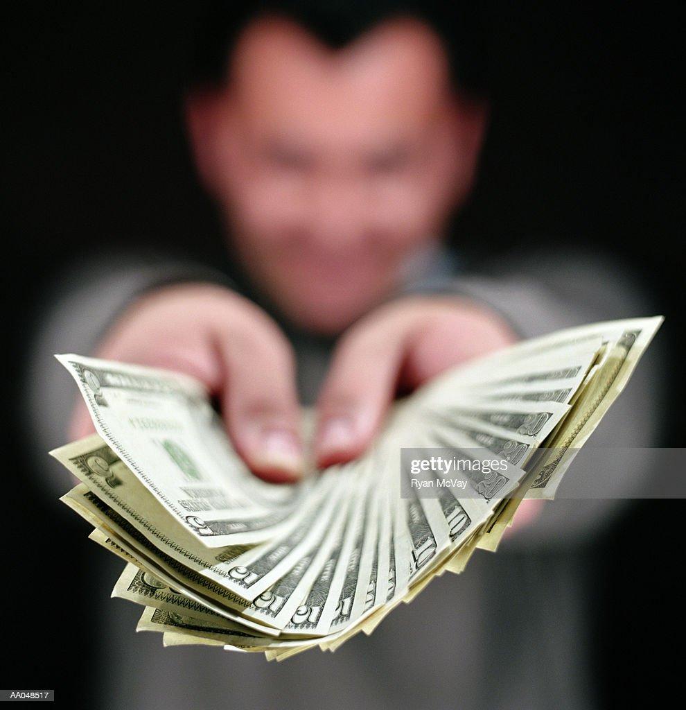 Man holding fan of assorted US dollar bills, focus on money : Stock Photo