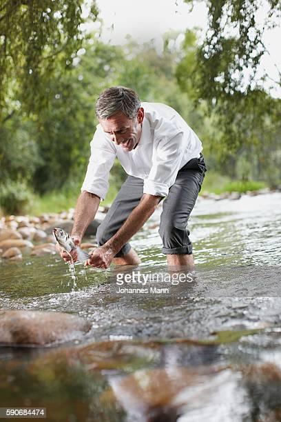 Man Holding Fish in Stream