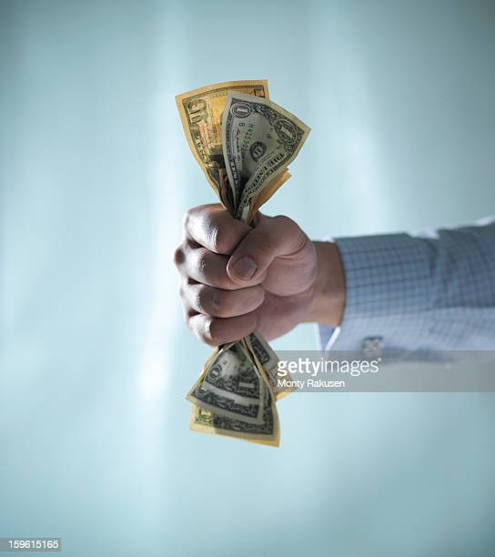man holding fistful of us dollar bills - greed stock pictures, royalty-free photos & images