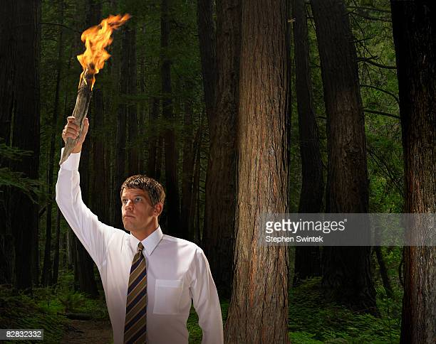 Man holding flaming torch in dark forest