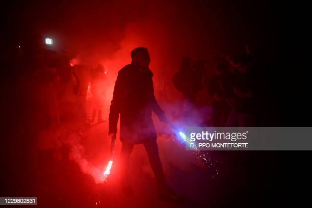 Man holding flare bombs takes part in a gathering of fans and people outside the San Paolo stadium in Naples on November 26, 2020 to mourn the death...