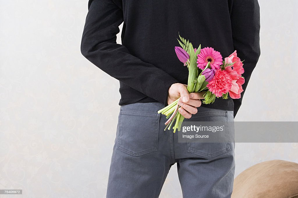 Man holding flowers behind back : Stock Photo