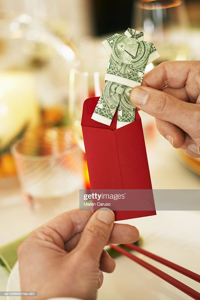 Man holding folded currency and red envelope, close-up : Stockfoto
